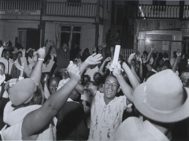 Description: British Honduras. 'Supporters of the Peoples United Party cheer wildly outside the offices of the Belize Times newspaper at 2 am in the morning after hearing that their party had won the British Honduras general election'. Photograph No R 34164 Official British Honduras photograph compiled by Central Office of Information. Crown copyright reserved. Publicity statement on reverse.